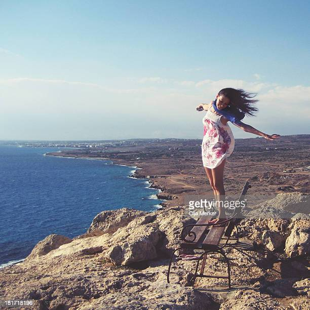 Young woman stands on top of a mountain