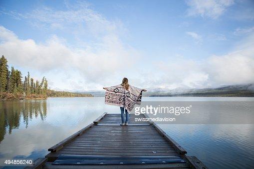 若い女性は木製の埠頭に腕を広げる