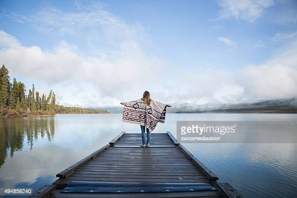 Young woman stands on wooden pier arms outstretched