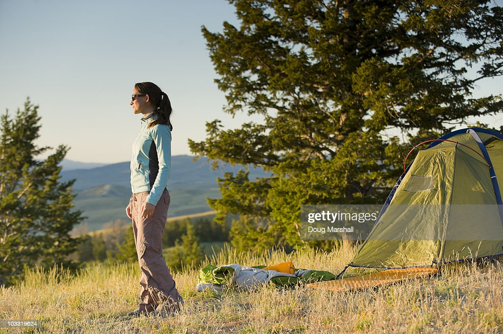A young woman stands outside her tent on a summer evening.