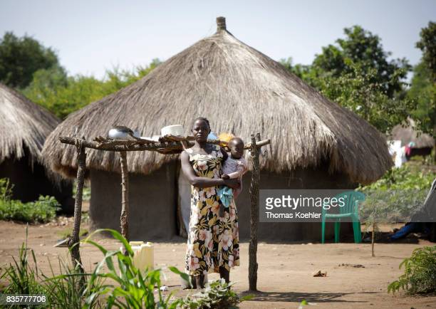 A young woman stands with her toddler in front of a hut at the Rhino Refugee Camp Settlement in northern Uganda The area is home to about 90000...