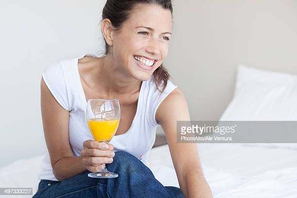 Young woman starting her day with glass of orange juice