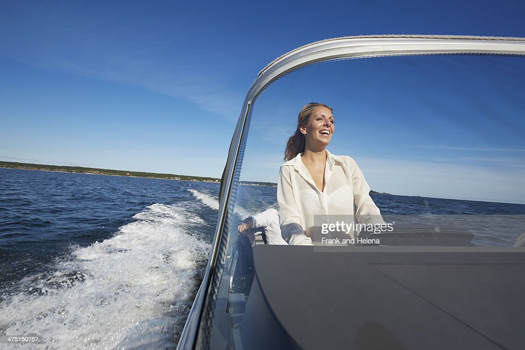 Young woman steering boat, Gavle, Sweden