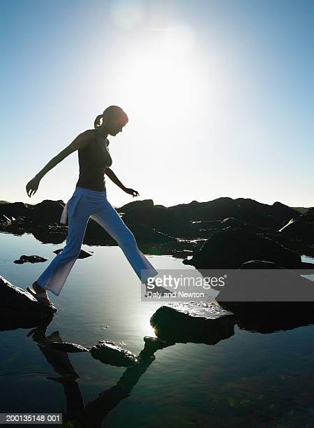 Young woman stepping across rocks over shallow water