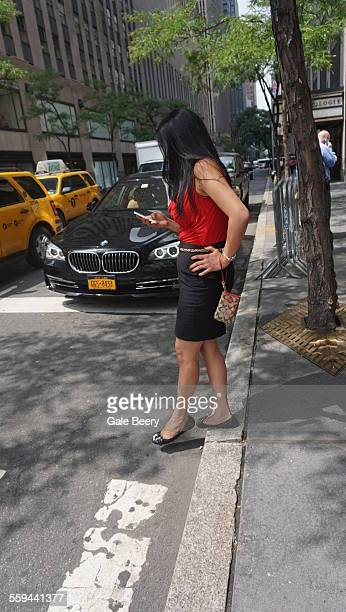 Young woman stepping Off curb in New York City Looking down at her cell Phone
