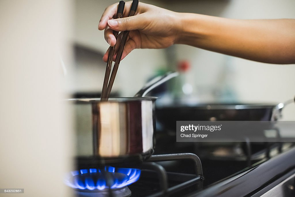 Young woman stirring pan on cooker top with chopsticks