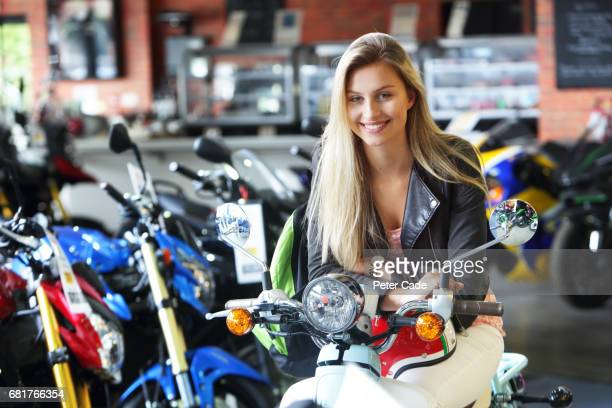 Young woman stood with scooter and helmet in showroom