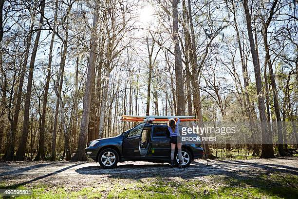 Young woman strapping paddleboard to roof of car
