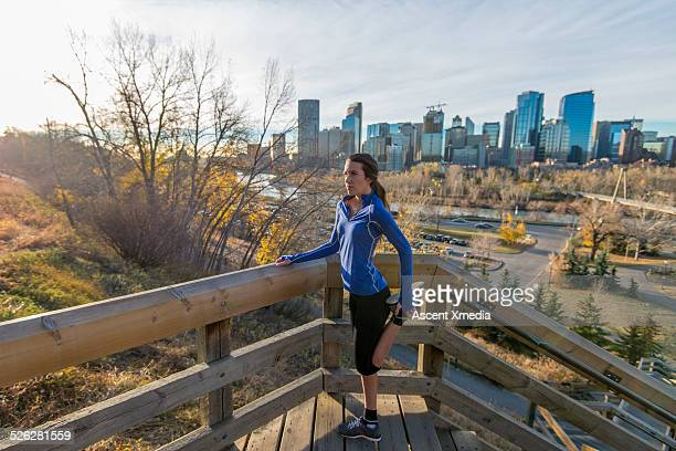 Young woman stretches before running stairs, city