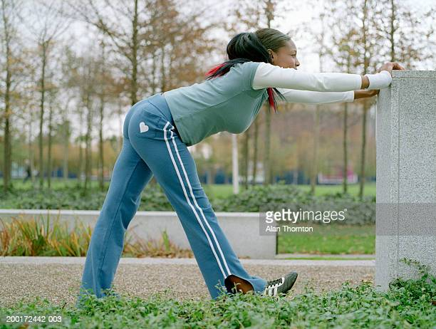 Young woman stretching against concrete block, side view