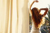 Young woman stretching arms, looking out window, rear view