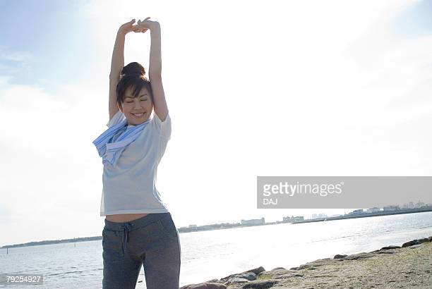Young Woman Stretching Her Arms, Low Angle View, Copy Space
