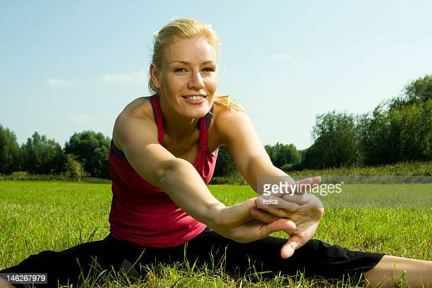 Young woman stretching in meadow