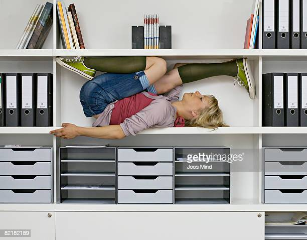 young woman stretching in office shelves
