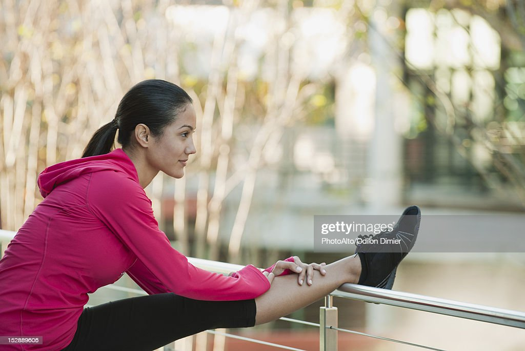 Young woman stretching leg on railing : Stock Photo