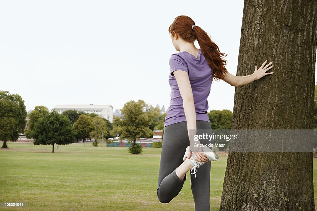 Young woman stretching leg,in park
