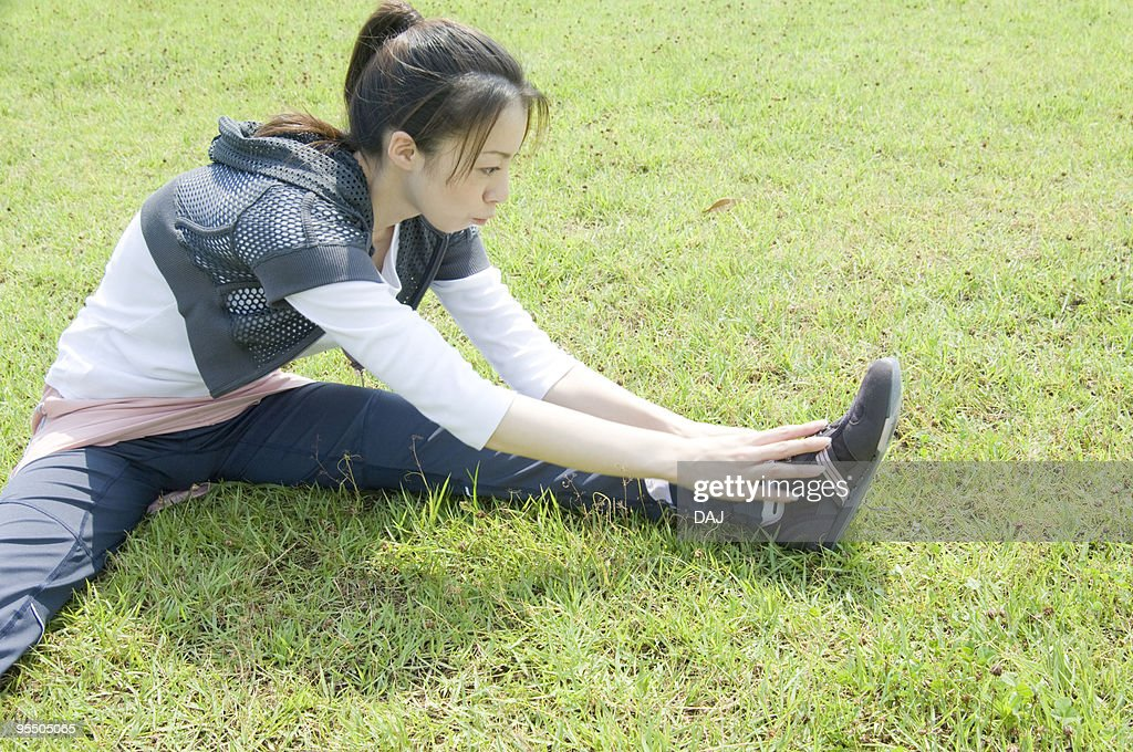 A Young Woman Stretching On The Grass : Stock Photo