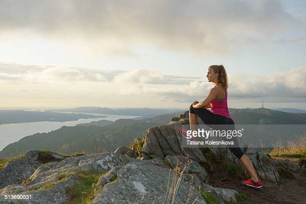 Young woman stretching on top of mountain