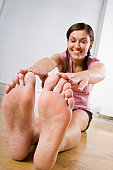 Young woman stretching, touching toes (focus on soles of feet)