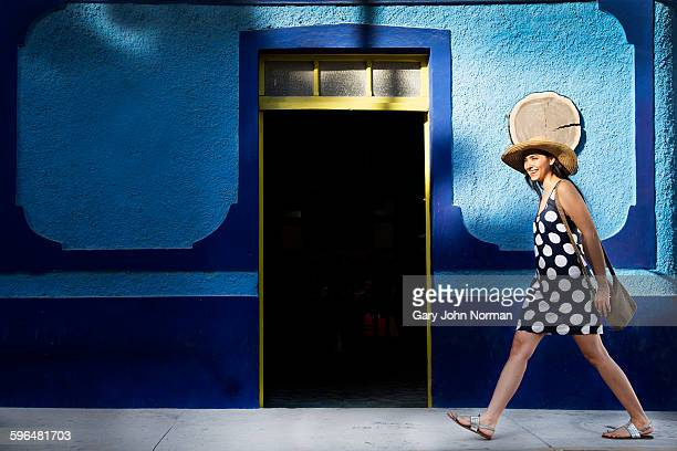 Young woman striding past blue wall in Mexico