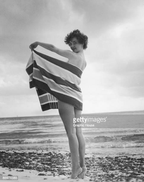 A young woman strikes a tantalizing pose behind a beach towel circa 1955
