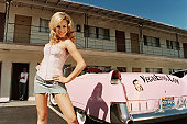 Young Woman Striking a Pose Next to a Pink Convertible