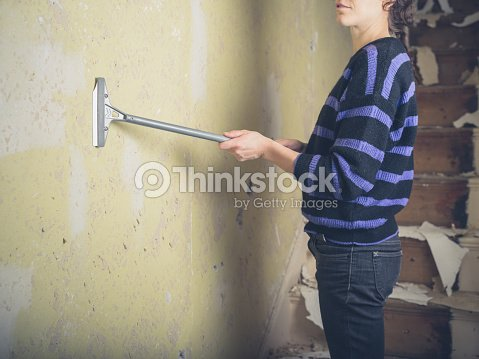 Young Woman Stripping Wallpaper Stock Photo