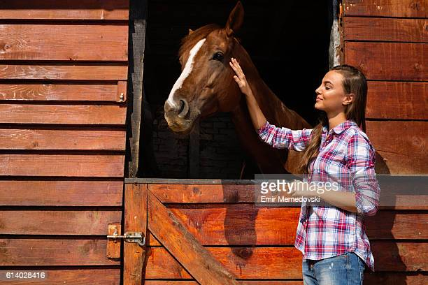 Young woman stroking a brown horse.