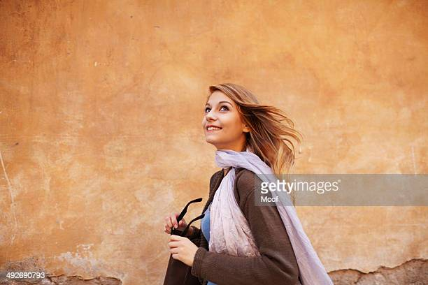 Young woman strolling down street looking sideways