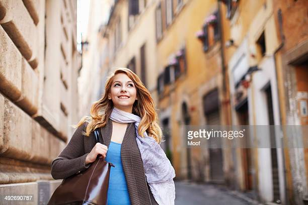 Young woman strolling down street, Rome, Italy