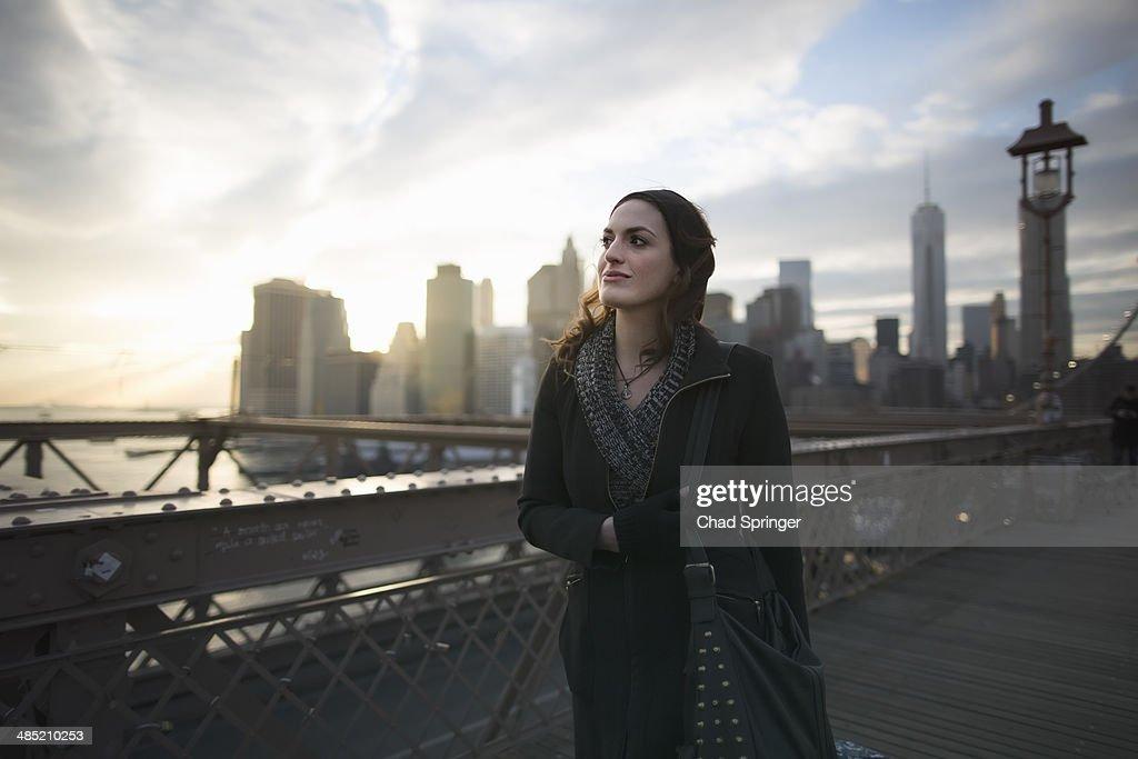 Young woman strolling on Brooklyn bridge, New York, USA