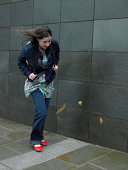 Young woman struggling to walk against wind