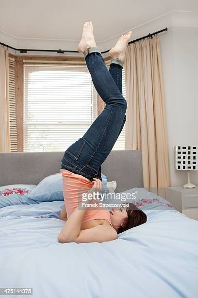 Young woman struggling to zip jeans on bed