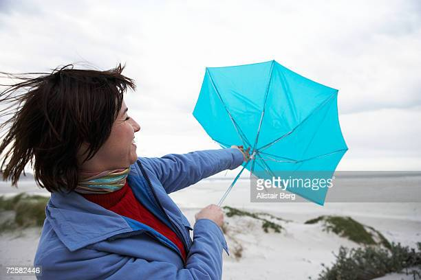 Young woman struggling with umbrella, against wind on dunes
