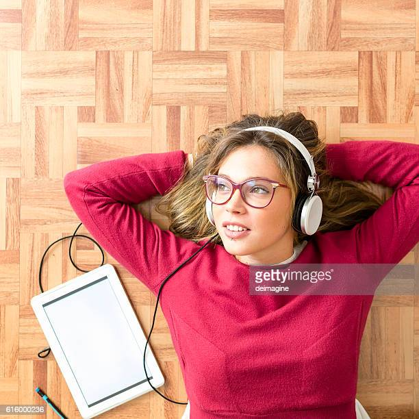 Young woman student listening lesson with device and headphone