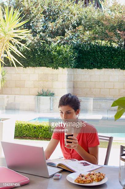 Young woman studying and having snack in garden