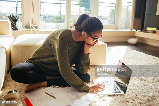 young woman studying and working on her laptop