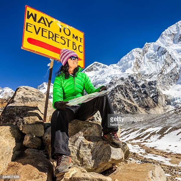 Young woman studying map next to signpost, Nepali Himalaya