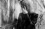 Young woman suffering from a severe disorientation, confusion, or sadness outdoors, in front of a wall. Converted to black and white, grain added, blurry, slightly out of focus.