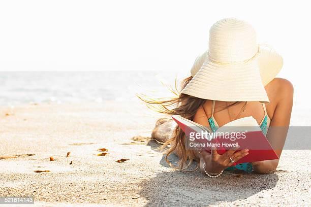Young woman sunbathing and reading book on beach, Malibu, California, USA