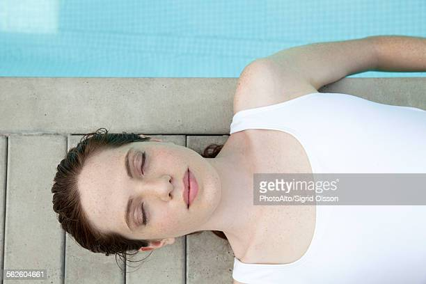 Young woman sunbathing by pool with eyes closed, overhead view