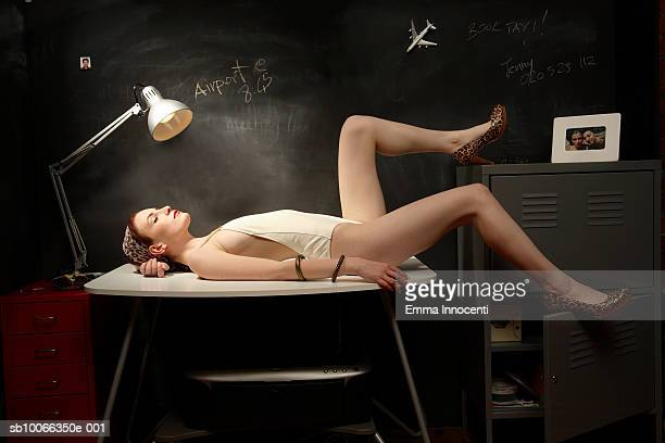 Young woman sunbathing in office under desk lamp, side view