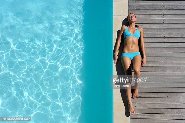 Young woman sunbathing on at poolside, view from above
