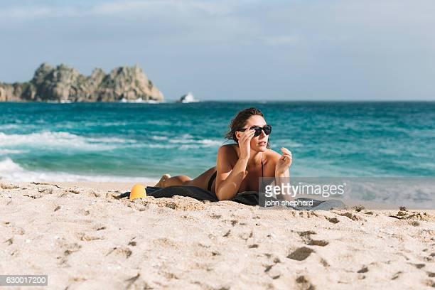 Young woman sunbathing on Porthcurno Beach, Cornwall.