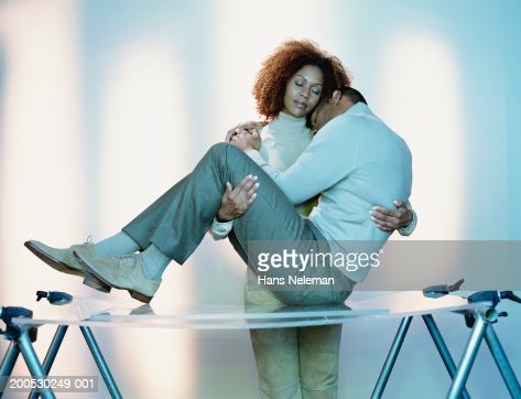 Young Woman Supporting Man On Ironing Board Stock Photo Getty Images