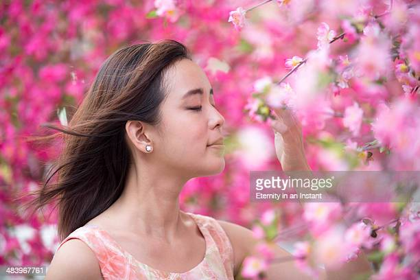 Young woman surrounded by pretty pink flowers