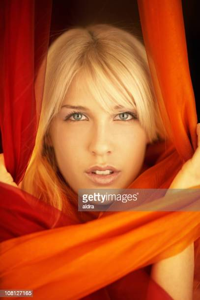 Young Woman Surrounded by Red Silk Fabric