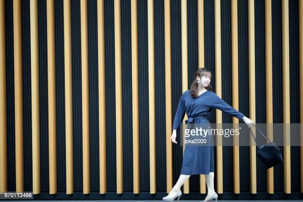 壁の前に袋を振る若い女性