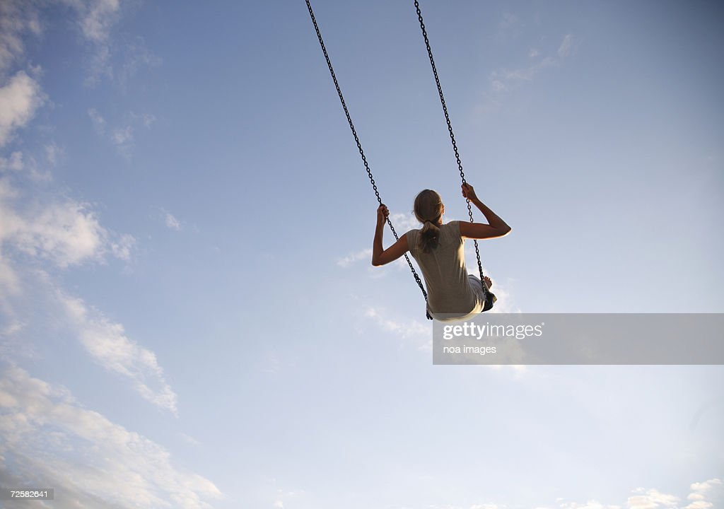 Young woman swinging on swing, rear view, low angle view