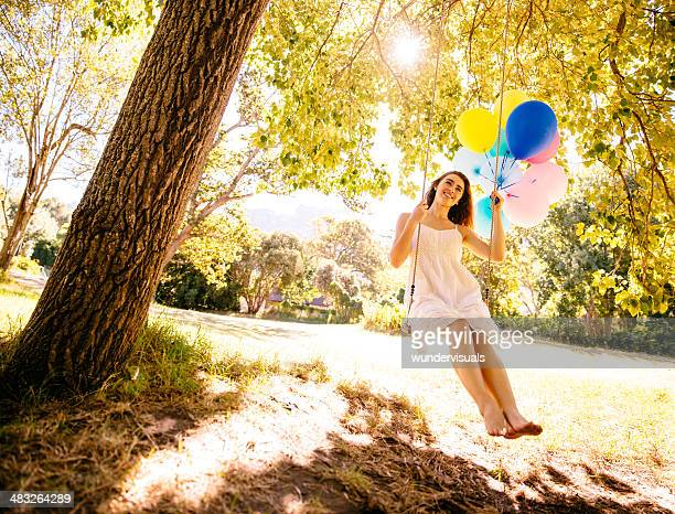 Young woman swinging with colorful balloons